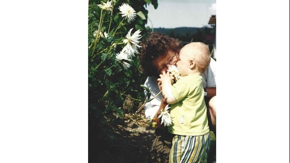 A toddler and his grandmother with some white flowers.